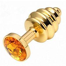 Золотистая пробка с рёбрышками и оранжевым кристаллом - 7 см.  Небольшая анальная втулка выполнена из металла и имеет размеры, подходящие для ношения и использования новичками, ребрышки-спирали добавляют острых ощущений обоим партнерам.