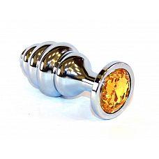 Серебристая пробка с рёбрышками и оранжевым кристаллом - 7 см.  Небольшая анальная втулка выполнена из металла и имеет размеры, подходящие для ношения и использования новичками, ребрышки-спирали добавляют острых ощущений обоим партнерам.