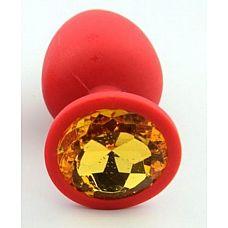 Красная анальная втулка с желтым кристаллом - 7,3 см.   Гладенькая силиконовая пробка с кристаллом в ограничительном основании.